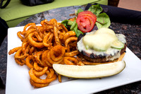 Grilled Elk burger with fresh sliced Jalapenos and seasoned curly fries